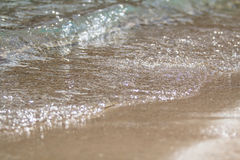 A espuma e a areia borbulhantes do mar na praia Fotografia de Stock Royalty Free