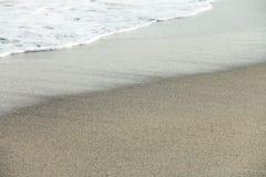 Espuma próxima da onda na praia Fotografia de Stock