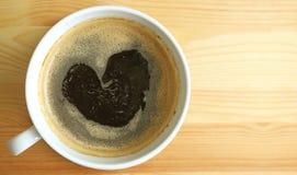 Espuma quente do café preto da forma do coração, vista superior com espaço livre na tabela de madeira para o projeto Imagens de Stock