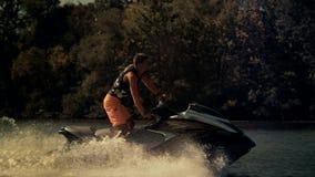 Esquí activo del jet del montar a caballo del hombre en el día soleado El jinete que salta en el esquí del jet en ondas almacen de video