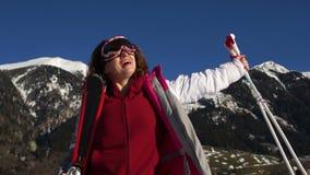 Esquí activo joven de la mujer en montañas Esquiador de sexo femenino con las gafas y los polos de seguridad que disfruta de día  almacen de metraje de vídeo