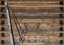 Esquí azul histórico con los polos en la pared de madera foto de archivo