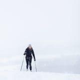 Esquí a campo través de la mujer joven en una nieve Imagen de archivo libre de regalías