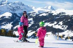 Esquí de la madre y del pequeño niño en montañas de las montañas La mamá y el niño activos embroman con el casco de seguridad, la foto de archivo