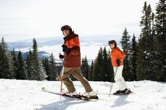 Esquí de los pares en cuesta de montaña Fotografía de archivo