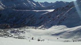 Esquí del hombre en montañas nevosas en la estación del invierno El esquí del paisaje se arrastra con un cielo azul en un día cla