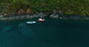 Esquí del jet que circunda cerca de la situación anaranjada brillante del catamarán del yate en laguna almacen de metraje de vídeo