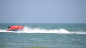 Esquí del jet que tira del barco del pez volador del plátano con los turistas que se divierten en él almacen de video