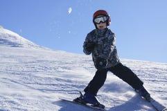 Esquí del niño y bola de nieve que lanza Imágenes de archivo libres de regalías