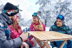 Esquí, diversión del invierno - familia que goza en bebida caliente en la estación de esquí Fotografía de archivo libre de regalías