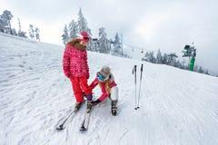 Esquí, diversión-madre del invierno que se prepara para la hija de esquí Fotos de archivo