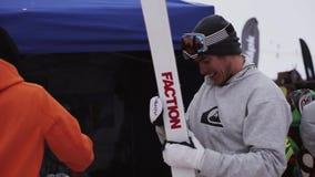 Esquí feliz de la fijación del esquiador por el destornillador en estación de esquí Sonrisa en cámara holidays metrajes