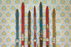 Esquís usados coloridos del vintage delante del papel pintado retro Imagen de archivo