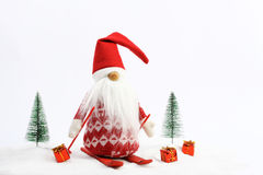Esquí del ayudante de la Navidad (duende) en nieve después dos árboles nevosos y tres colores del regalo rojo y blancos Foto de archivo