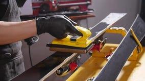 Esqu? o concepto de la adaptaci?n y del reapair de la snowboard Trabajador de la tienda del invierno que hace la reparaci?n y el  metrajes