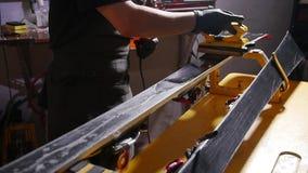 Esqu? o concepto de la adaptaci?n y del reapair de la snowboard Trabajador de la tienda del invierno que hace la reparaci?n y el  almacen de metraje de vídeo