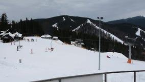 Esqu? y snowboard de la gente en cuesta de la nieve en estaci?n de esqu? del invierno Elevador del esqu? en la monta?a de la niev almacen de metraje de vídeo