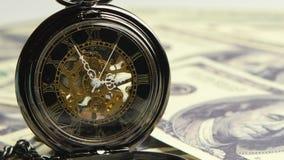 Esqueleto do relógio em um fundo do dinheiro Fim acima