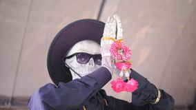 Esqueleto en sombrero negro y las gafas de sol que ruegan las manos dobladas Estatua para Dia De Los Muertos Mexican Holiday 4K almacen de video