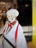 Esqueleto en un vestido médico blanco imagenes de archivo