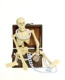 Esqueleto que senta-se no TRAJETO de GRAMPEAMENTO da caixa de tesouro fotos de stock