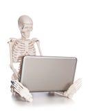 Esqueleto que trabaja en el ordenador portátil Imagenes de archivo