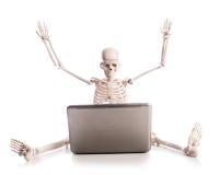 Esqueleto que trabaja en la computadora portátil Foto de archivo libre de regalías