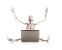 Esqueleto que trabaja en la computadora portátil Fotos de archivo libres de regalías