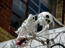 Esqueleto y bici en un tejado en SoCo Imagen de archivo libre de regalías