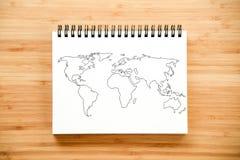 Esquema del mapa del mundo en el cuaderno Foto de archivo libre de regalías