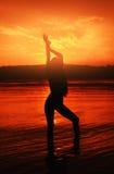 Esquema del ` s de la muchacha en fondo de la puesta del sol imagen de archivo libre de regalías