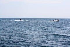 Esqui aquático pelo barco no mar fotografia de stock