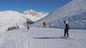 Esqui da mulher de dois esquiadores que cinzela o estilo na inclinação de montanha no inverno video estoque