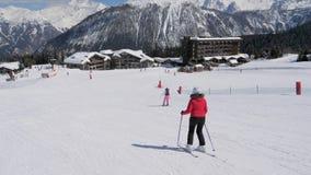 Esqui do esquiador que cinzela o estilo nas montanhas no fundo da inclinação o chalé vídeos de arquivo