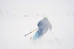 Esqui do homem novo na tempestade de neve imagem de stock