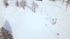 Esqui e snowboarding das atividades do inverno na opinião aérea da inclinação da neve Povos no elevador do esqui na opinião do za filme