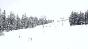 Esqui e snowboarding dos povos abaixo de uma inclinação do esqui video estoque