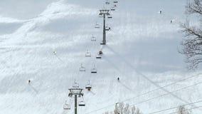 Esqui e snowboarding dos povos na inclinação da neve na estância de esqui do inverno Elevador do esqui na montanha da neve Ativid video estoque