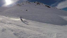 Esqui rápido do esquiador abaixo do pó da neve do pulverizador do monte em voltas vídeos de arquivo
