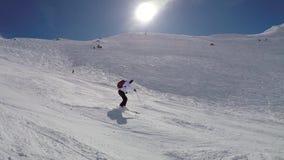 Esqui rápido do esquiador ativo abaixo do pó da neve do pulverizador do monte em voltas video estoque