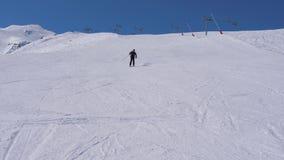 Esquiador activo, con adrenalina en su sangre, tallando rápidamente abajo de la cuesta del esquí almacen de metraje de vídeo
