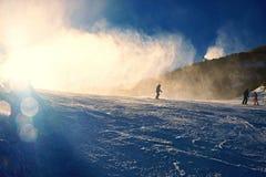 Esquiador cerca de un cañón de la nieve que hace nieve del polvo Estación de esquí de las montañas Foto de archivo libre de regalías