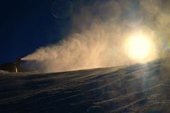 Esquiador cerca de un cañón de la nieve que hace nieve del polvo Estación de esquí de las montañas Imágenes de archivo libres de regalías