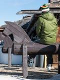 Esquiador con las botas de esquiar que se relajan en el caballo del banco de madera formado Imagen de archivo libre de regalías