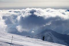 Esquiador cuesta abajo en las nubes de tormenta de la cuesta y de la luz del sol del esquí Foto de archivo libre de regalías