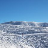 Esquiador cuesta abajo en cuesta nevosa del esquí en la mañana agradable del sol Fotos de archivo libres de regalías