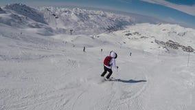Esquiador da mulher adulta que esquia para baixo com dificuldade na inclinação da montanha no inverno filme