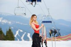 Esquiador da mulher na parte superior do monte nevado com os esquis na estância de esqui Imagem de Stock
