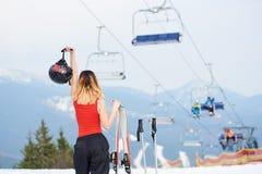 Esquiador da mulher na parte superior do monte nevado com os esquis na estância de esqui Fotografia de Stock