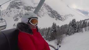 Esquiador da mulher que vai acima no recurso de Ski Lift In The Mountains no inverno vídeos de arquivo